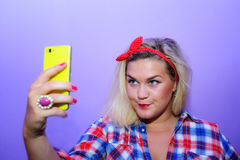 Pretty blog girl with blue eyes making selfie with her yellow smartphone Stock Images