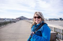 Pretty blond adult female stands on the Tybee Island pier, bundled up in a winter jacket. In winter stock image