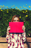 Pretty blond book covers his beautiful smile shameless. Portrait of charming young woman with pink book held up close to her face, cute female covering half face Stock Photo