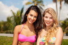 Pretty blond and brunette girls outdoors. Pretty blond and brunette young women wearing bikini bathing suits outdoors in a park setting with palm trees in the Stock Photo