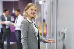 Pretty blond businesswoman opens a door in modern office. Concep Royalty Free Stock Photography
