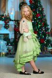Pretty blond child-girl on the background of a New Year tree Royalty Free Stock Photos