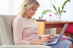 Pretty blond female printing in laptop while sitting in armchair Stock Photo