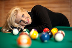 Pretty blond girl with billiard balls Stock Images