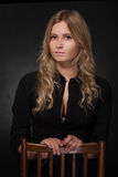 Pretty blond girl. In black blouse at dark Stock Photography