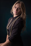 Pretty blond girl. In black with necklace at dark Royalty Free Stock Photography