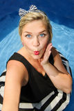 Pretty blond girl with blue eyes in retro dress making selfie in swimming pool Royalty Free Stock Image