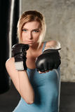 Pretty blond girl in boxing gloves. Royalty Free Stock Photography