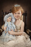 Pretty blond girl with a doll Royalty Free Stock Photo