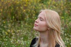 Pretty blond girl enjoying nature. Pretty blond girl with eyes closed enjoying nature Stock Images
