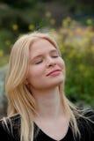 Pretty blond girl enjoying nature. Pretty blond girl with eyes closed enjoying nature Royalty Free Stock Photo