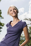 Pretty blond girl enjoying a summers day. Low angle portrait of a slender pretty blond girl enjoying a summers day looking up into the air with a joyful smile Royalty Free Stock Photography