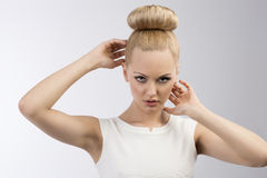 Pretty blond girl with hairstyle. Very cute blond woman with white dress and hair-style on gray background Stock Image