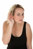 Pretty Blond Girl Hard of Hearing. Young hard of hearing woman with her hand cupping her ear to hear Royalty Free Stock Image