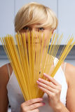 Pretty blond girl in the kitchen making pasta Royalty Free Stock Images