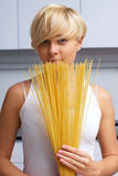 Pretty blond girl in the kitchen making pasta Stock Photos
