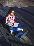 Pretty blond girl with long hair sitting in the stadium with a book and a computer Royalty Free Stock Image