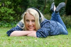 Pretty Blond Girl Lying on Grass with Earphones Royalty Free Stock Photos