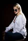 Pretty blond girl in a man`s shirt and sunglasses posing on a dark background Royalty Free Stock Photo