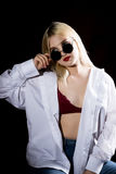 Pretty blond girl in a man`s shirt and sunglasses posing on a dark background Royalty Free Stock Photography