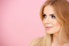 Pretty blond girl over pink with copyspace Stock Photography