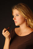 Pretty blond girl with pipe Royalty Free Stock Images