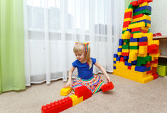 Pretty blond girl playing with colored blocks in kindergarten Stock Photos