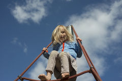 Pretty blond girl playing on rope of red web in summer stock photos