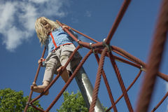 Pretty blond girl playing on rope of red web in summer royalty free stock photography