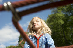 Pretty blond girl playing on rope of red web in summer stock image