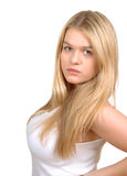 Pretty blond girl posing on white background. Beautiful blond girl posing on white background. She is dressed in white tank top. She has a serious facial royalty free stock photo