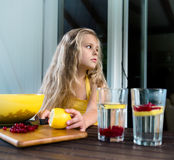 Pretty blond girl is preparing berry drink from a lemon and red currant Stock Images