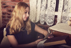 Pretty blond girl reading a book and looking at the photo Stock Images