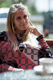 Pretty blond girl sitting in a cafe. Pretty blond girl sitting in a café thinking of something royalty free stock photography