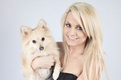 Pretty blond girl sitting with is dog on the sofa Royalty Free Stock Photos