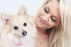 Pretty blond girl sitting with is dog on the sofa Stock Photo