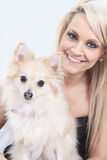 Pretty blond girl sitting with is dog on the sofa Royalty Free Stock Image