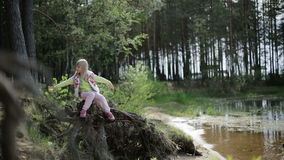 Pretty blond girl sitting on an old tree stump with roots on the bank of the lake. The child makes smooth movements with hands. The beautiful nature in the stock video footage