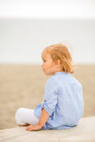Pretty blond girl sitting overlooking the sea. Pretty little blond girl sitting with her back to the camera looking to the side on a wall overlooking the sea and Stock Photos