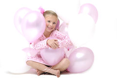 Pretty blond girl sitting between pink balloons Royalty Free Stock Images
