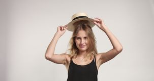 Pretty blond girl in straw hat video. Lauging cutie in black camisole briefly lifts her hat on white background stock footage