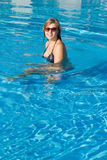 Pretty blond girl swimming in pool Stock Photos