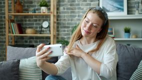 Pretty girl taking selfie with smartphone camera at home posing touching hair. Pretty blond girl is taking selfie with smartphone camera sitting on sofa at home stock footage