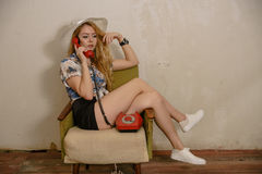 A pretty blond girl is talking by phone. A pretty caucasian girl in a hat is talking by phone in an armchair Stock Image