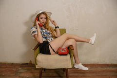 A pretty blond girl is talking by phone. A pretty caucasian girl in a hat is talking by phone in an armchair Royalty Free Stock Image
