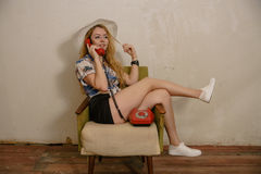 A pretty blond girl is talking by phone Royalty Free Stock Images