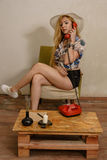 A pretty blond girl is talking by phone Royalty Free Stock Image