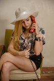 A pretty blond girl is talking by phone. A pretty caucasian girl in a hat is talking by phone in an armchair Royalty Free Stock Photography