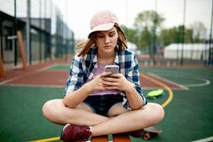A pretty blond girl wearing checkered shirt, pink cap and denim shorts is sitting cross-legged on the sports field and royalty free stock photography