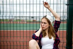A pretty blond girl wearing checkered shirt, white cap and denim shorts is sitting leaned on the guardlattice on the royalty free stock photos